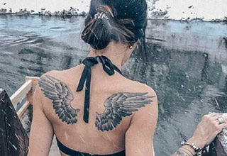 a woman with angel wing tattoos standing in front of a snow covered pond
