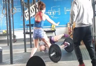 a woman in red workout top and blue shorts runs over to a man who is laying on the ground by a barbell
