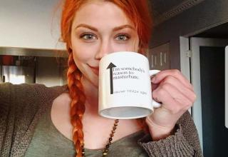 a beautiful redhead with a mug that says im someone's reason to masturabte