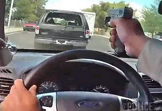 a cop holding his gun at a suv in front of him while driving