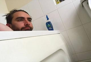 man in bathtub looking sad and bored