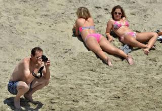 a man at the beach taking pictures and two women in bikinis giving him dirty looks