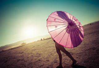 Woman in the desert covers her breasts with an umbrella, but you can see the silhouette of her nipple through the umbrella.