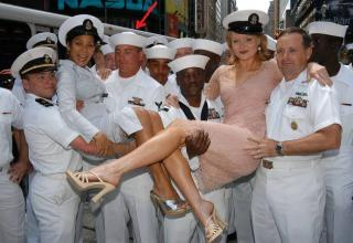 a bunch of navy sailors holding two women in the air and one sailer is staring at the womans boobs