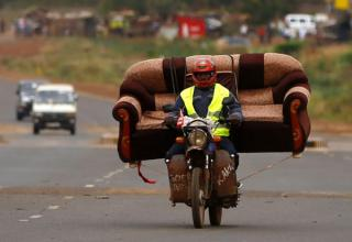man carrying couch on motorcycle