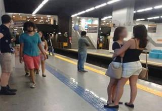 Girls hug each other romantically at a subway station.
