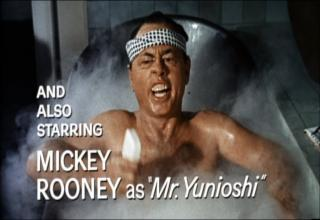 Mickey Rooney sitting in a bathtub, looking asian, wearing a hachimaki, curling his upper lip inward to expose his upper teeth, and holding a bar of soap. Text: and also starring Mickey Rooney as Mr. Yunioshi.