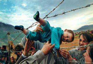 a young boy is passed through a barbed wire fence because of a border dispute