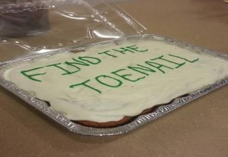 A cake with writing on it in frosting: Find the toenail