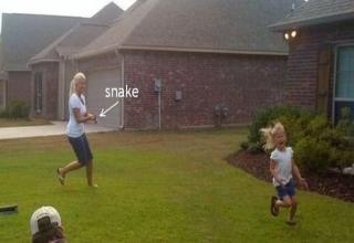 Mom chases frightened daughter in front yard with a snake.