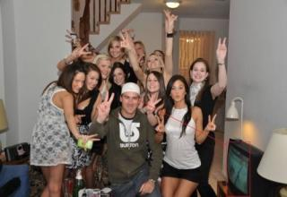 Guy poses for a picture with a bunch of babes, but he's watching hockey on TV.