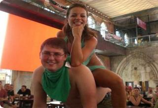 Girl in a bikini sits on a friend's back. he's smiling and looks patheti