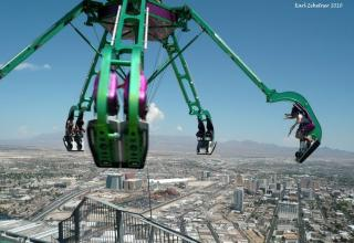 a weird, scary ride swings in a circle far above a city-scap