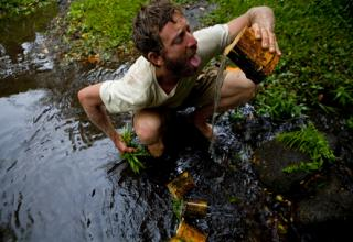 Man squatting in swamp, drinking water out of a home-made cup.