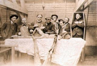 Sepia tone picture of men in suits standing around corpses. Text: Medical students with cadavers. Date unknown