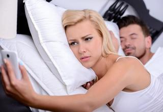 woman laying in bed on cell
