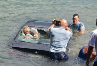 A woman gasps for breath in the back of a car that is sinking into the water. Two police officers struggle to get into the car to save her.