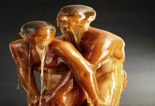 A man hugs a woman from behind. They are both naked and completely covered in honey.
