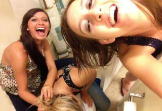 Girls laughing into a camera while another girl vomits.