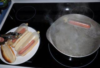 Hot dogs being cooked in con