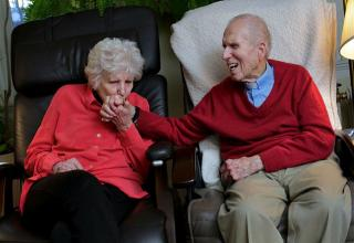 elderly couple holding hands sitting on couch