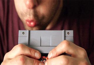 man blowing on NES cartridge