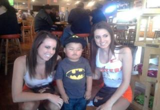 a little boy staring at a hooters waitress