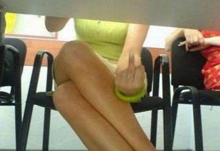 girl giving middle finger under desk