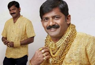 Indian man wearing a gold shirt and gold necklaces.