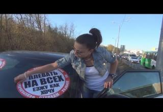 Pictured: Woman trying to peel sticker off her car. Text: -Think better next time! -I'm gonna f*cking run you over!