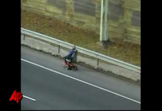 Old Man Rides Down Highway in Wheelchair view on ebaumsworld.com tube online.