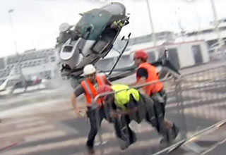 While erecting a seven story high structure, the helicopter's rotor struck a cable causing the aircraft to crash to the ground. The Pilot was helped from the crumpled wreckage with minor injuries. Both of my Panasonic P2HD camera's were recording at the same time.