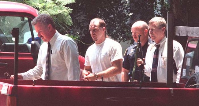 Hank Carr (center), who later used a hidden key to escape incarceration and murdered the two detectives on the left and far right. Carr then led cops on a high-speed chase before being killed in a standoff.