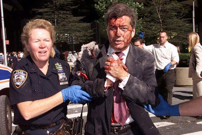 NYPD Officer Moira Smith helps an injured man on the morning of 9/11/2001. Shortly after the photo was taken, she returned to the lobby of the south tower. She was killed ten minutes later when the building collapsed.