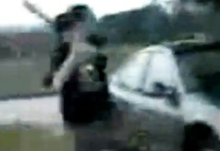 a man attacking a car with a bat