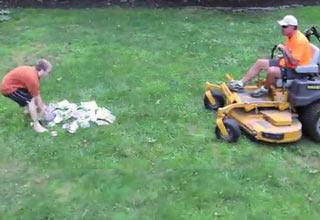 An angry father runs over his son's video game collection with a lawn mower.