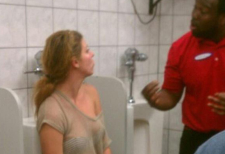 employee talks to indignant woman sitting in a urinal.