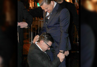 A fan holds Leonardo DiCaprio around the waist. They are both wearing suits and smiling. Leo is standing upright as if he's not super comfortable.