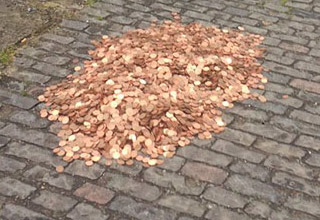 390 dollars worth of mixed copper coins on sidewalk