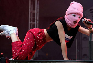 girl in pink ski mask and red pants singing