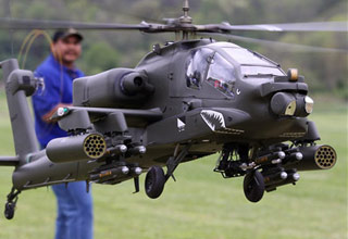 a man wearing all blue looking at the camera while flying his remote controlled apache helicopter