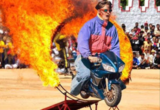 a man jumps a flaming hoop on a mini bike
