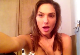 Actress Gal Gadot touching her neck while lip-syncing | gal gadot lip syncing while wearing a bra