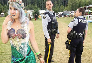 a woman in mermaid outfit and a male cop staring at him while a female cop stars at the male cop