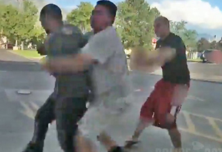 a man in a gray shirt grabs another man who attacked a police officer and fled