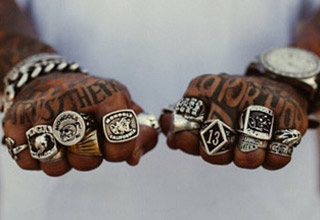 a man with a bunch of motorcycle gang rings on his fingers