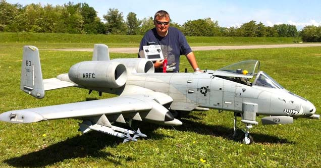 a massive mibo thunderbolt rc plane in a field with a guy standing over it