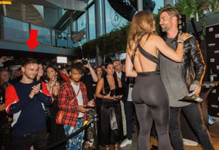 a man in a crowd applauding a womans plump rear end