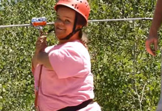 a woman with dwarfisim on a zipline wearing a pink helmet, shirt, and bluejeans