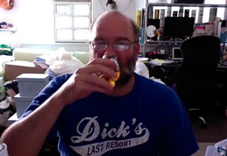 a man sipping whiskey in his cluttered home